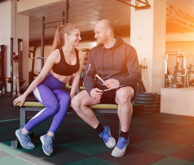 パーソナルトレーニングの概念。ベンチに座っているスポーティな金髪の女性を訓練するノートブックの結果のインストラクターのメモ。笑顔のスポーツカップル