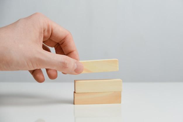 Концепция поэтапного планирования. рука держит деревянные блоки на белом пространстве.