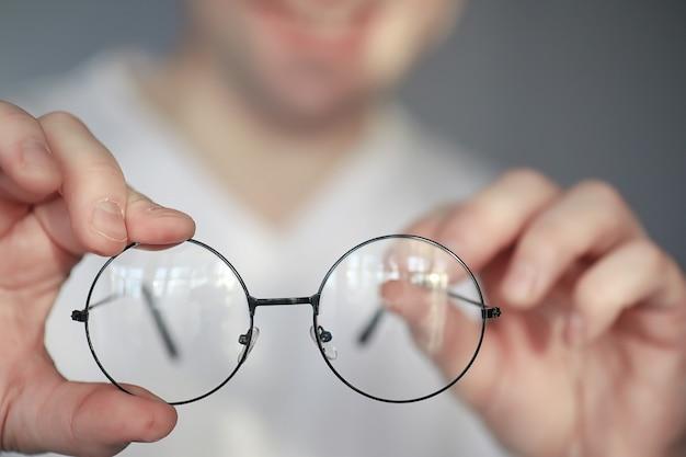 가난한 시력의 개념입니다. 콘택트 렌즈와 안경을 손에 잡으십시오. 안경 및 렌즈 광고 포스터.