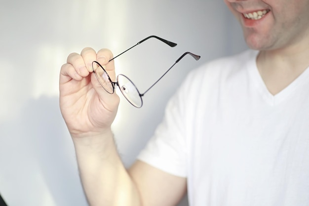 視力低下の概念。コンタクトレンズとメガネを手に持ってください。メガネやレンズの宣伝用ポスター。