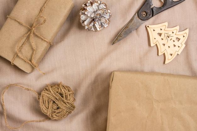 クリスマスと新年の贈り物を準備するという概念。はさみ、ひも、木製のクリスマスツリー、ベージュのテーブルに包装紙で包まれたギフト付きの箱。コピースペースのあるフラットレイ。