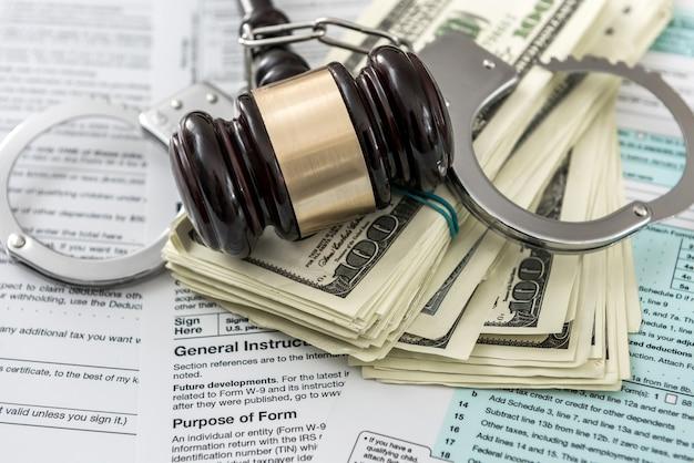 법 문제의 개념. 미국 1040 세금 양식에 수갑이 든 경찰 수갑