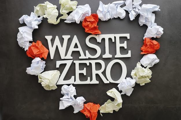 適切な環境衛生の概念。木製の文字と紙の要素と黒の背景に碑文。無料のgmo。ゼロウェイスト。