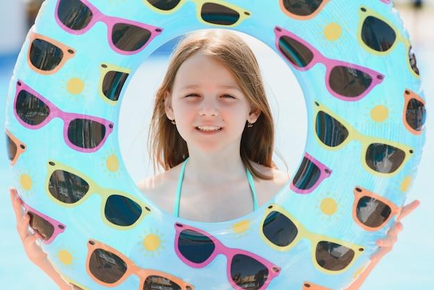 海でのレクリエーションの概念。女の子はプールサイドで泳ぐための膨脹可能な円を保持します