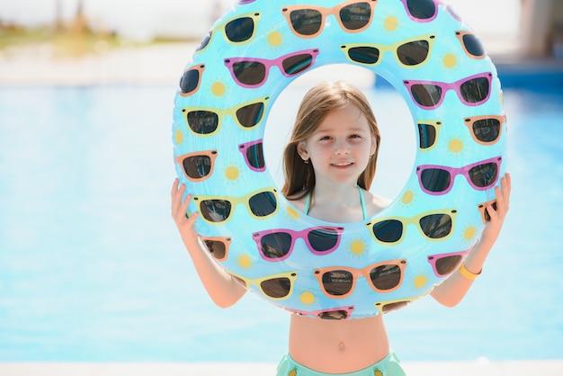 Концепция отдыха на море. девушка держит надувной круг для плавания у бассейна