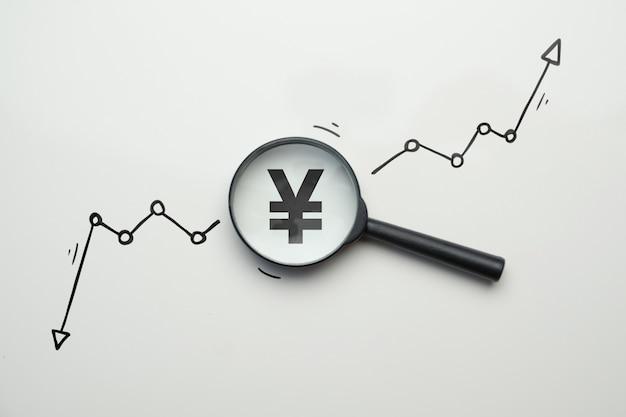 Концепция исследования динамики роста и падения валюты йены в стеклянной лупе.