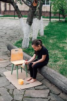 Концепция повторного использования старых вещей ребенок перекрашивает старый стул желтой краской
