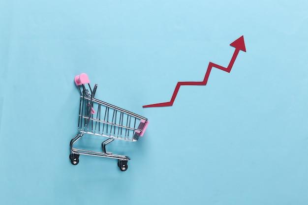 Концепция роста продаж. тележка для покупок со стрелкой роста на синем