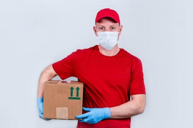 Концепция безопасной доставки. курьер в красной форме и защитной медицинской маске и перчатках держит картонную коробку, бесконтактная доставка заказов