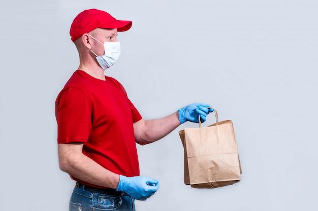 Концепция безопасной доставки. курьер в красной форме и защитной медицинской маске и перчатках держит бумажный пакет, бесконтактную доставку заказов