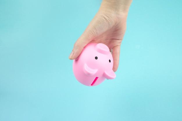 쇼핑에 돈을 절약의 개념 손 그것에서 돈을 꺼내 핑크 돼지 저금통을 뒤집었습니다.