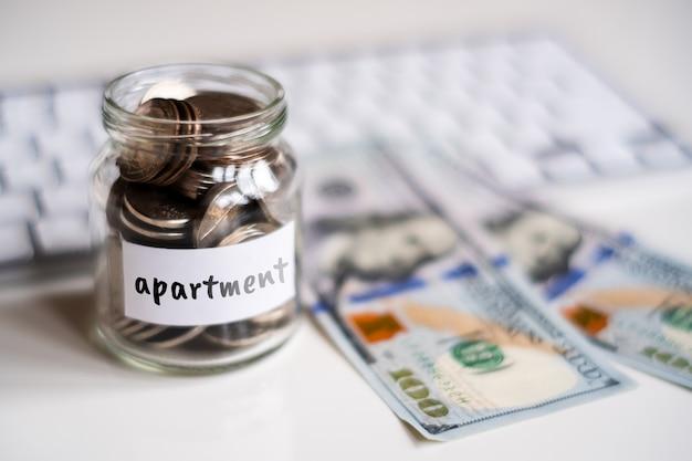 アパートのための節約の概念-コインと碑文が付いているガラス瓶。