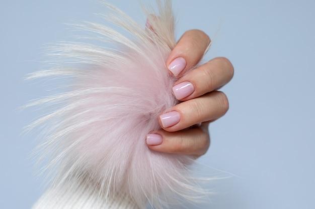 セルフケアビューティーのコンセプトヌードカラーのすっきりとしたマニキュアを備えた女性の手