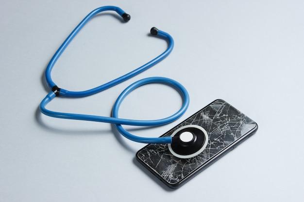 Концепция сервисной помощи при поломке смартфона. разбитое стекло экрана смартфона, стетоскоп на сером столе