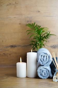 スパとアロマセラピーのコンセプト-木製のテーブルにアロマリードで作られたキャンドル、タオル、ディフューザー