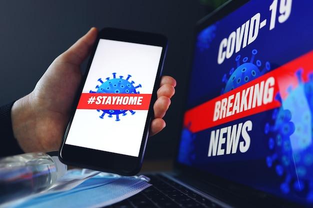Концепция оставаться дома - это эпидемия коронавируса covid-19. антисептическая маска для лица и телефона. экран ноутбука covid-19 последние новости фон.