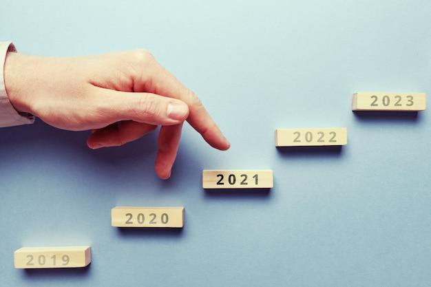 Концепция успеха и роста из года в год. рука над прямой лестницей.