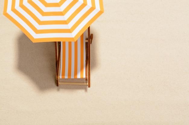 여름 휴가의 개념. 모래 해변에서 우산 아래 일광욕 의자에 상위 뷰