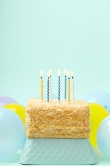 축하의 개념, 촛불과 다채로운 풍선이 있는 생일 케이크, 밝은 파란색 배경.