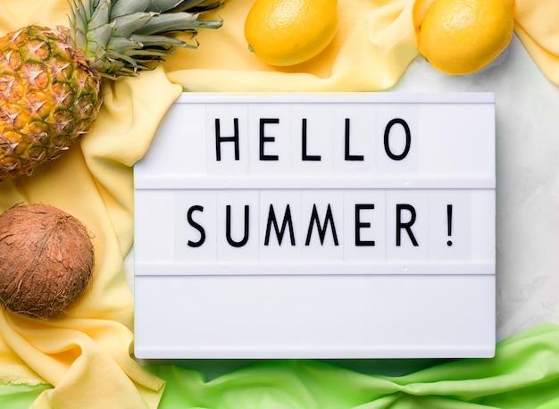 Концепция наступающего лета. лайтбоксы с надписью привет лето рядом с тропическими фруктами