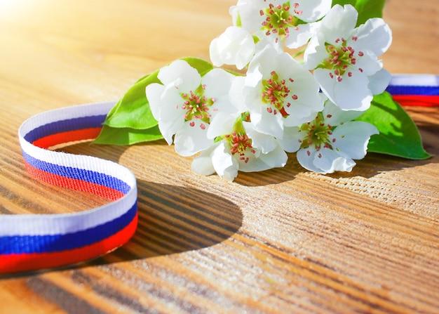 Концепция дня россии. лента нарисована в цветах российского флага и ветки цветущего дерева на деревянной поверхности.