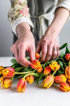 꽃집 작업의 개념. 여자는 노란색, 주황색, 빨간색 튤립 꽃다발을 만든다.