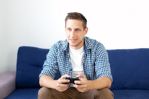 ゲームのコンセプト。男は自宅でジョイスティックを使ってビデオゲームをプレイしています。ソファに座ってシャツを着た笑顔の男がジョイスティックでビデオゲームをします。コンピュータゲームの競争。ゲーマー。