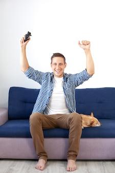ゲームのコンセプト。男は犬と一緒に自宅でジョイスティックを使ってビデオゲームをプレイしています。ソファに座ってシャツを着た笑顔の男がジョイスティックでビデオゲームをします。ゲーマー。コンソール、ゲーム
