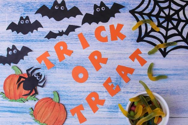 ハロウィーンの休日の概念。碑文のトリックまたはトップビューを扱う青い背景のコウモリとお菓子