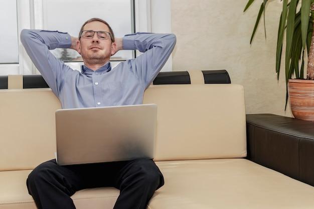 仕事中の休息の必要性の概念。青いシャツを着た疲れたマネージャーは、ラップトップを膝に抱えながら満足してストレッチします。