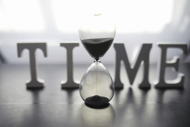 시간의 흐름의 개념입니다. 어두운 배경에 모래 시계입니다. 비문 시간. 단어 표면의 그림자.