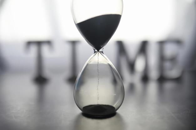 Понятие о течении времени. песочные часы на темном фоне. время надписи. тень на поверхности слова.