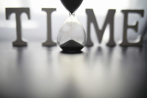 어두운 배경 비문 시간에 시간의 흐름의 개념 모래 시계