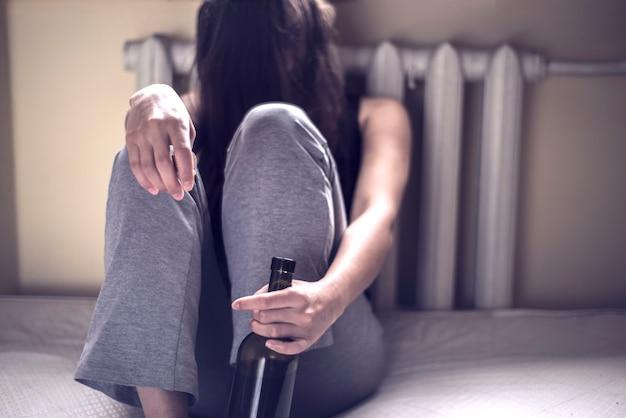 여성 알코올 중독의 문제의 개념 어린 소녀는 와인 한 병과 그녀의 손에 유리로 된 머리카락이있는 더러운 방에 앉아 있습니다. 알코올 과다 복용