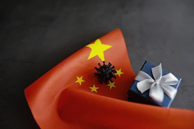 세계 코로나바이러스 전염병의 개념. 바이러스의 지리적 위치. 중국 국기와 바이러스 모델 및 선물 상자.