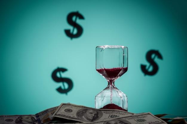 Концепция времени - деньги. песочные часы на кучу долларов. закройте вверх. знаки доллара