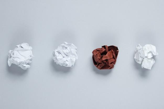 独自性、人種差別の概念。灰色のテーブルに白と茶色のしわくちゃの紙のボール。トップビュー、ミニマリズム