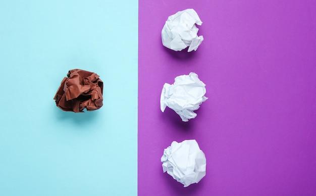 独自性、人種差別の概念。紫と青のテーブルに白と茶色のしわくちゃの紙のボール。ミニマリズム事業