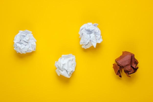 独自性、人種差別の概念。黄色のテーブルに白と茶色のしわくちゃの紙のボール。トップビュー、ミニマリズムビジネス