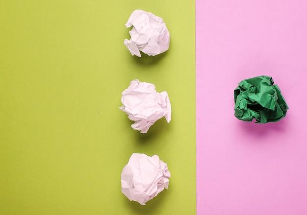 独自性、人種差別の概念。色付きの背景に白と緑のしわくちゃの紙のボール。ミニマリズムビジネス