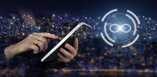 무제한 인터넷의 개념입니다. 도시의 어두운 배경에 디지털 홀로그램 무한대 기호가 있는 흰색 태블릿을 손으로 터치합니다. 개념 아이디어, 삶, 성공, 비즈니스.
