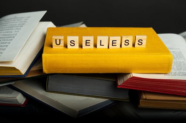 役に立たない知識の概念。役に立たない-木製のブロックからの言葉