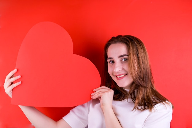 발렌타인 데이 또는 여성의 날의 개념. 그녀의 손에 큰 붉은 마음으로 어린 소녀. 공간을 복사하십시오. 사진 프레임.