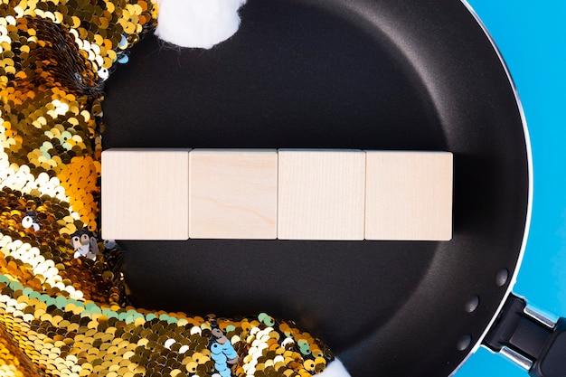 サンタクロースの鍋と帽子にある4つの木製の立方体にテキストを書くという概念。スペースをコピーします。