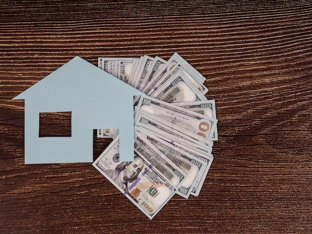 Концепция вашего дома или ипотеки. дом с купюрами на деревянной доске, плоская планировка