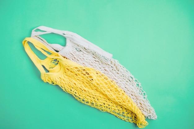 Концепция нулевых отходов без пластика. хлопковая многоразовая сумка для покупок из сетки на синем фоне.