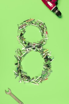 緑の背景に8月の女性の休日についての釘、ネジ、ツールのセットからの概念的な構成。装飾の数8。上面図。男性の職業の女性