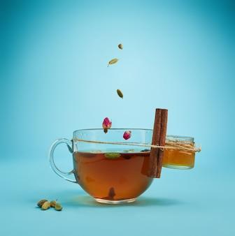 青い背景の上のハーブティー、蜂蜜、レモンのカップの概念的なイメージ
