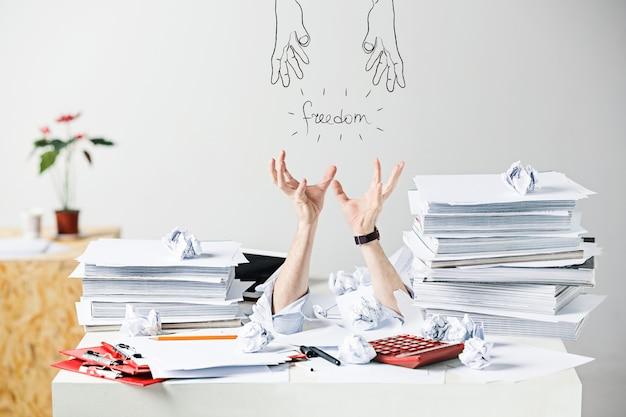 스트레스를 받는 남성 직장의 책상에 있는 많은 구겨진 종이에 대한 개념적 이미지 또는 콜라주