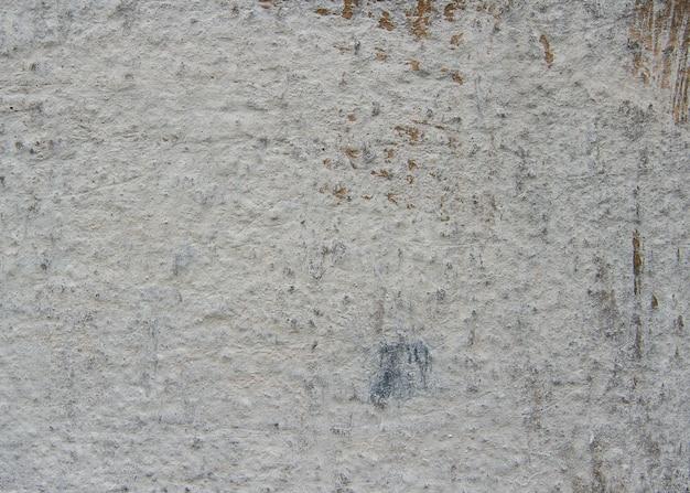 Бетонная стена покрыта серым облицовочным наполнителем. на старой стене царапины и потертости разных размеров.